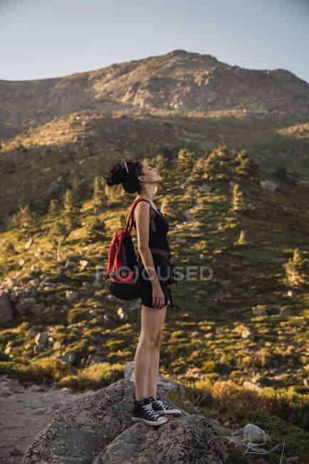 Vue latérale d'une belle femme mince avec sac à dos debout sur des rochers dans une vallée verdoyante profitant de la nature avec les yeux fermés — Photo de stock