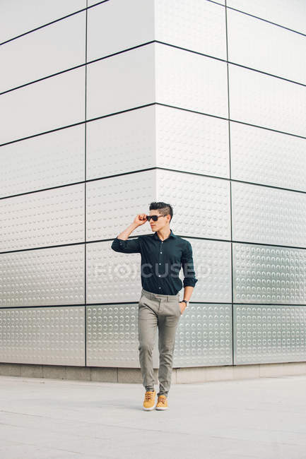 Casual man walking in front of modern building and looking away — Stock Photo