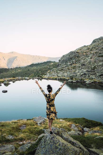 Donna su rocce di piccolo lago in montagna, vista posteriore — Foto stock