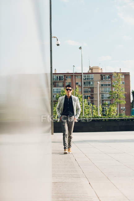 Confident elegant man walking in city with hands in pockets — Stock Photo