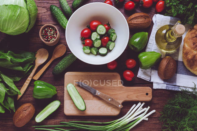 From above assortment of red and green ripe vegetables, salad in bowl and wooden cutting board. — Stock Photo