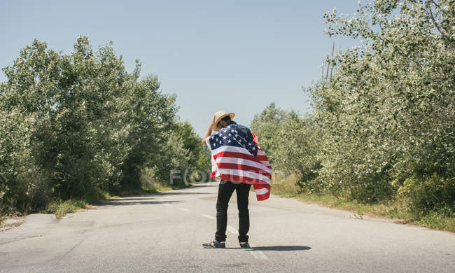 Man with American flag walking on road — Stock Photo