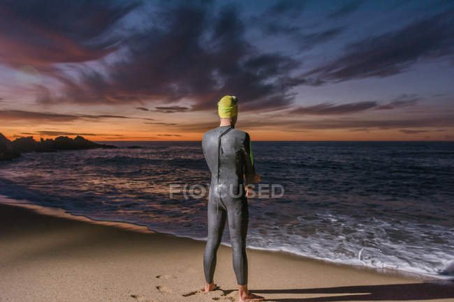 Triathlete standing at sea — Stock Photo