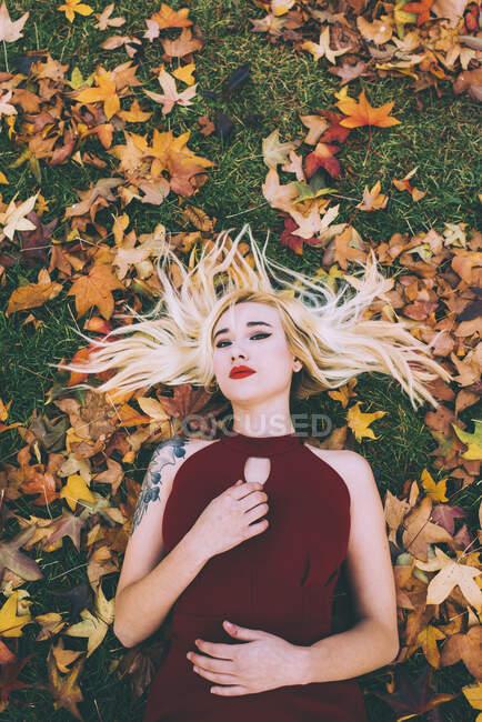 De cima mulher loira com braço tatuado deitado na grama verde em folhagem e olhando para a câmera. — Fotografia de Stock
