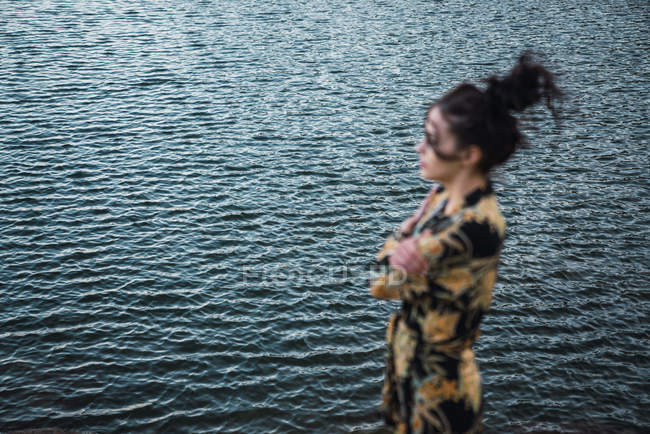 Young woman standing alone on shore, lake water in background — Stock Photo