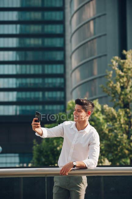 Jeune homme d'affaires prenant selfie avec smartphone contre bâtiment moderne — Photo de stock