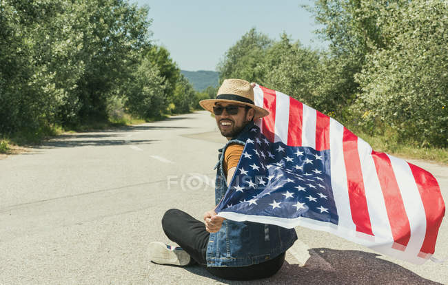 Homem com bandeira americana sentado na estrada — Fotografia de Stock