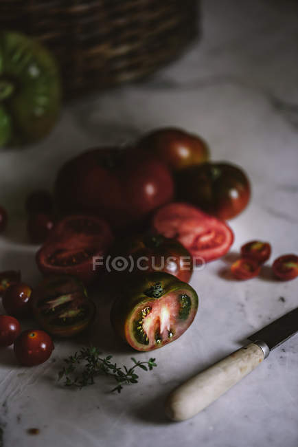 Fresh whole and halved tomatoes on white marble tabletop — Stock Photo