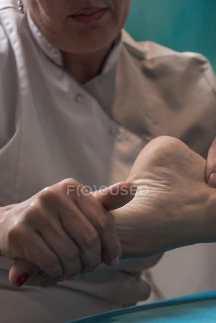 Terapeuta masaje pie femenino en sala de masajes - foto de stock
