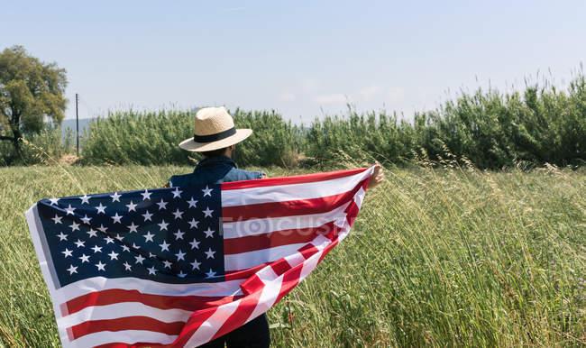 Человек, стоящий с американским флагом — стоковое фото