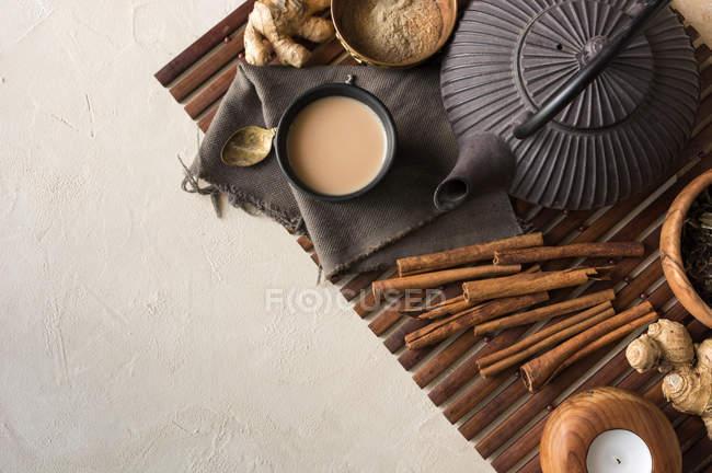 Tasse orientale de thé Chai au lait, cannelle, gingembre et cardamome sur tapis en bois — Photo de stock
