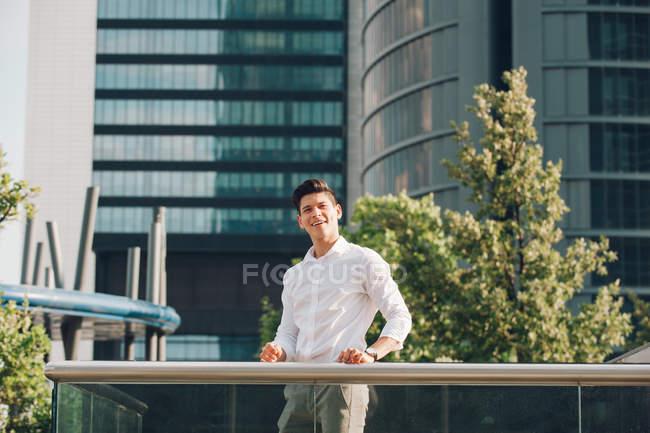 Giovane uomo d'affari sorridente in piedi vicino ringhiera contro edificio moderno — Foto stock