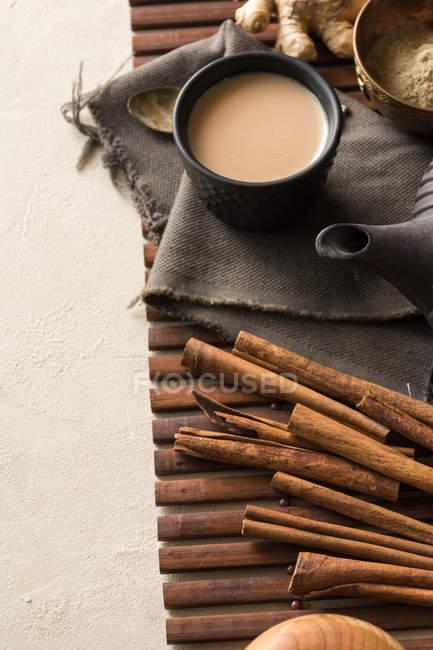 Oriental tasse de thé Chai avec lait, cannelle, gingembre et cardamome sur tapis en bois — Photo de stock