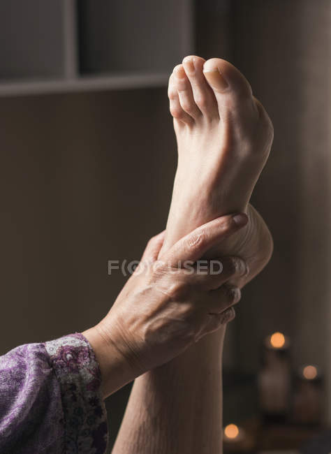 Therapist doing foot reflexology massage on female patient — Stock Photo