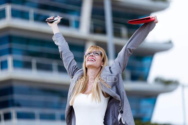 Giovane donna d'affari eccitato in piedi con le braccia contro edificio per uffici — Foto stock
