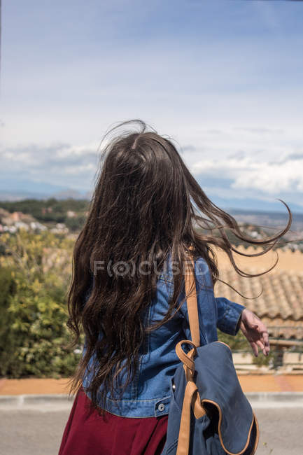 Girl with backpack standing on hill in town — Stock Photo