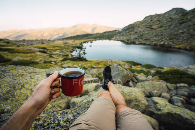Cropped of man with mug in hand on shore of lake — Stock Photo
