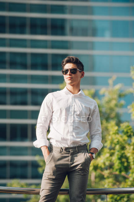 Confident young businessman standing against modern building — Stock Photo