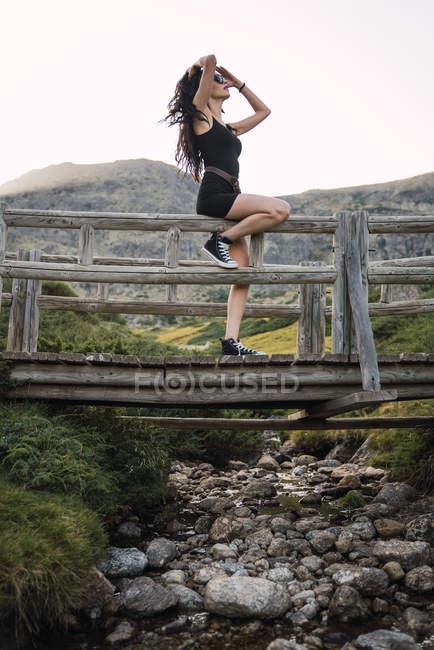 Тонкая женщина, сидящая на заборе над скалистой долиной — стоковое фото