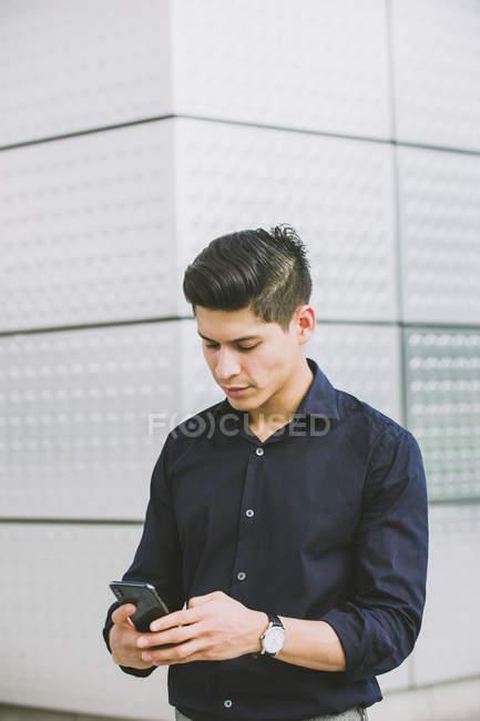 Homme élégant utilisant un téléphone portable tout en se tenant contre le mur du bâtiment — Photo de stock