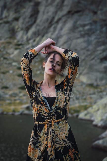 Молода жінка стоїть сама на березі в горах. — стокове фото