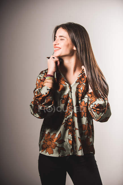 Laughing girl in patterned shirt posing on grey background — Stock Photo