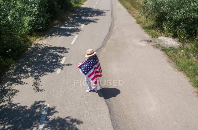 Женщина в шляпе идет с американским флагом по одинокой дороге. Специальный день для празднования 4 июля — стоковое фото