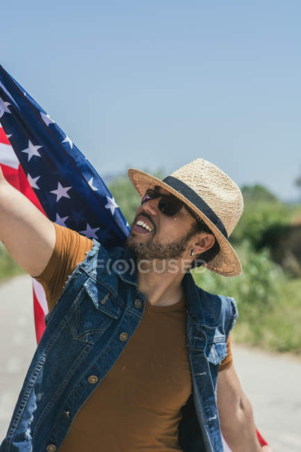 Man with American flag standing in field — Stock Photo