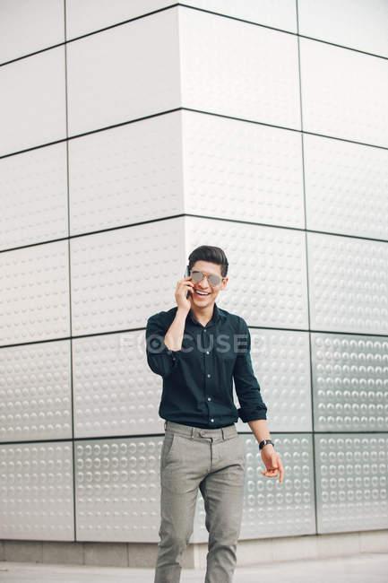 Alegre e jovem empresário falando no telefone contra a parede de construção — Fotografia de Stock
