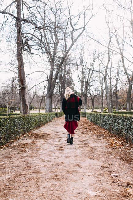 Jeune femme en robe rouge marchant dans le parc — Photo de stock