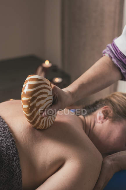 Therapist doing oriental massage with shell in massage room — Stock Photo