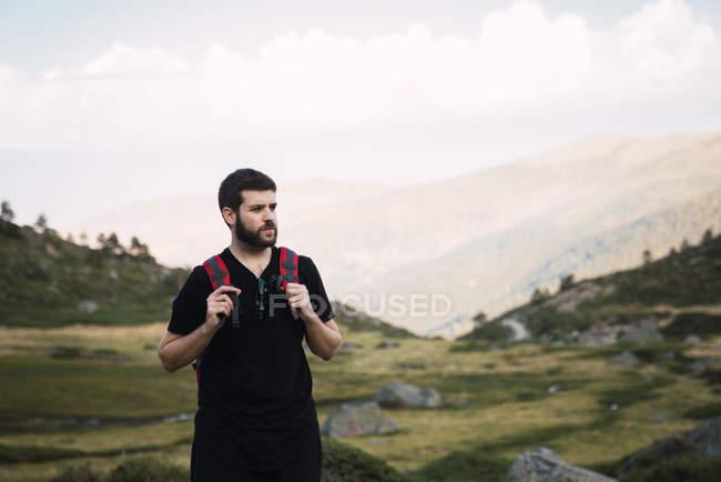 Взрослый бородатый мужчина с рюкзаком стоит в зеленой скалистой долине и смотрит в сторону, Испания — стоковое фото