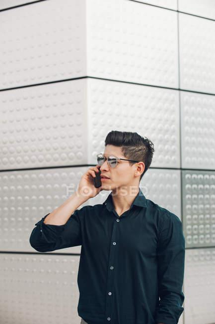 Jovem empresário falando no telefone contra a parede de construção — Fotografia de Stock
