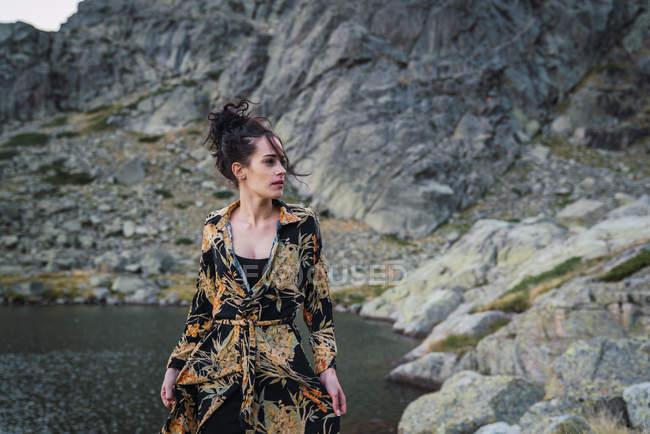Молода жінка стоїть одна на скелястому березі озера. — стокове фото