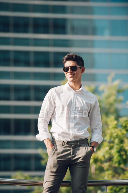 Empresário positivo contra edifício moderno — Fotografia de Stock