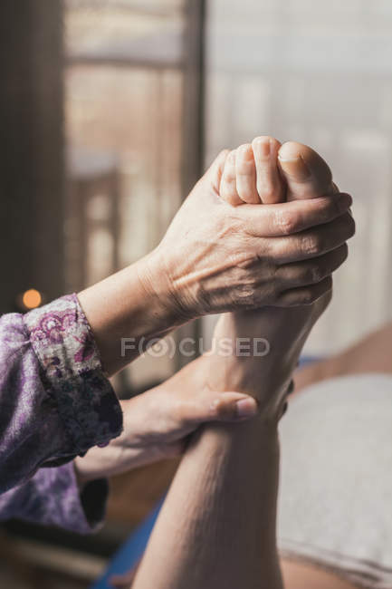 Terapista che fa massaggio riflessologico ai piedi su paziente donna — Foto stock
