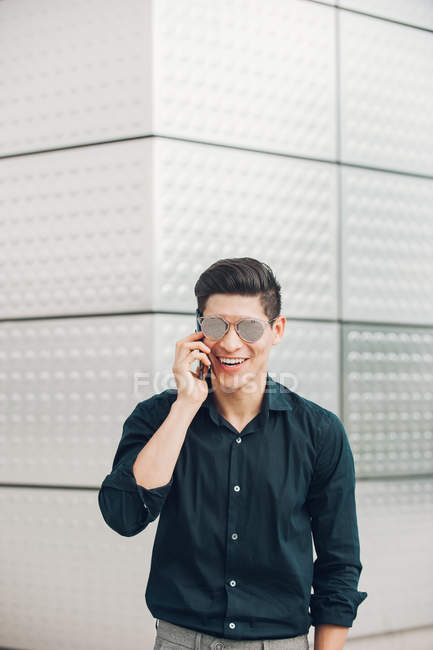 Cheerful young businessman speaking on phone against building wall — Stock Photo