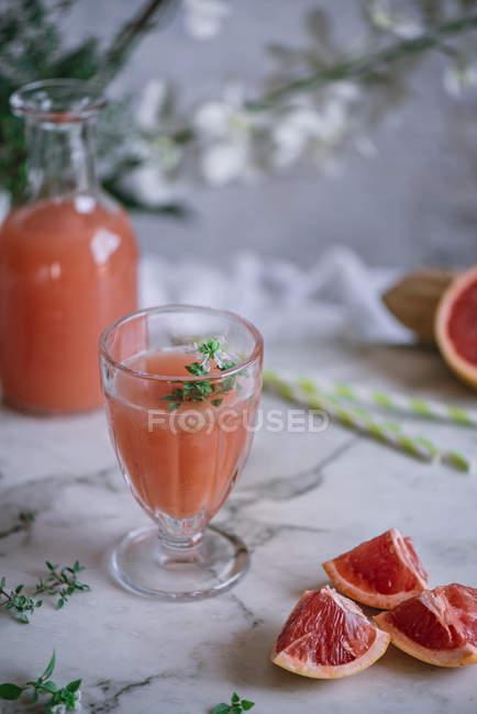 Jus de pamplemousse frais en verre sur la table de la cuisine le principe — Photo de stock