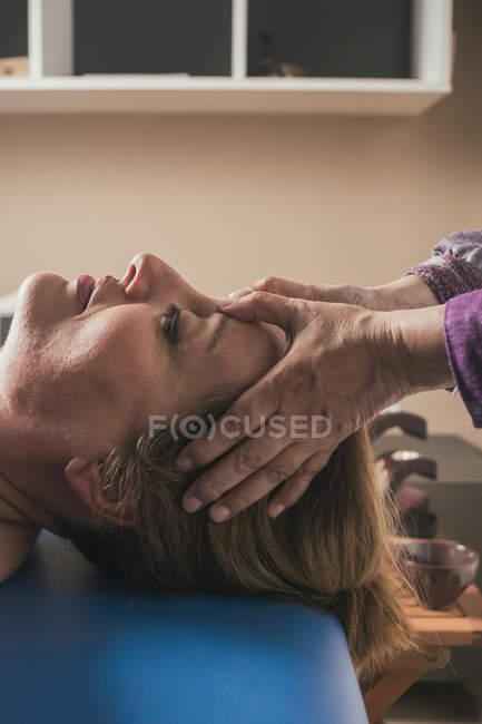 Terapeuta masajeando la cabeza femenina en sala de masajes - foto de stock