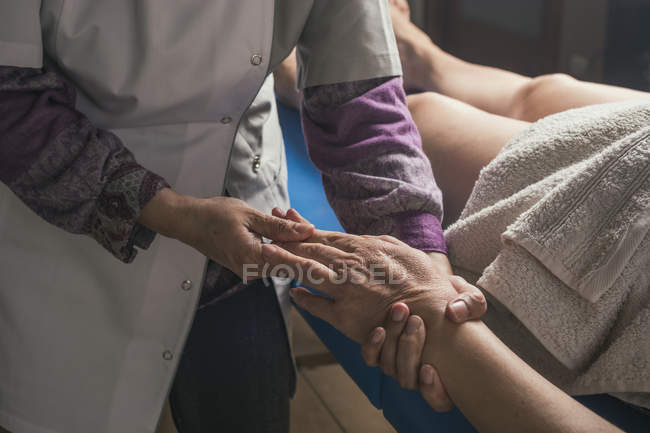 Therapist doing oriental massage to woman in massage room — Stock Photo