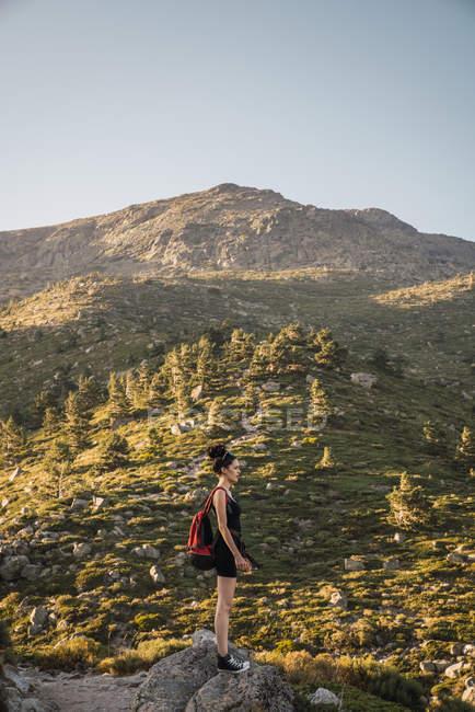 Jeune femme avec sac à dos profitant de la nature des montagnes — Photo de stock
