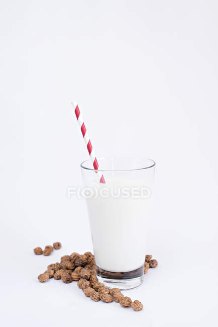 Heap of tasty raisins and glass of fresh milk with striped straw on white background — Stock Photo
