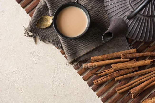 Tasse orientale de thé Chai au lait, cannelle et cardamome sur tapis en bois — Photo de stock