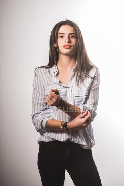 Young woman in shirt and jeans posing on grey background — Stock Photo