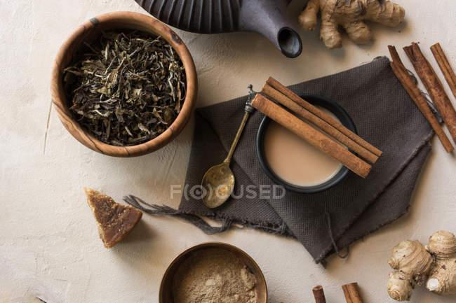 Tasse orientale de thé Chai au lait, cannelle, gingembre, poivre blanc et cardamome à la surface beige — Photo de stock