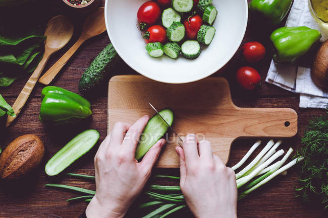 Вище асортимент червоних і зелених стиглих овочів і руки людини рубають огірки на дерев'яній дошці для різання.. — стокове фото