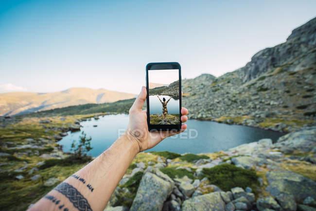 Mano di uomo tatuato che tiene smartphone come scattare foto di donna su rocce in piedi sulla riva del lago di montagna — Foto stock