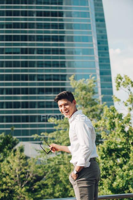 Смеющийся молодой бизнесмен, стоя против современных строительных и глядя через плечо — стоковое фото