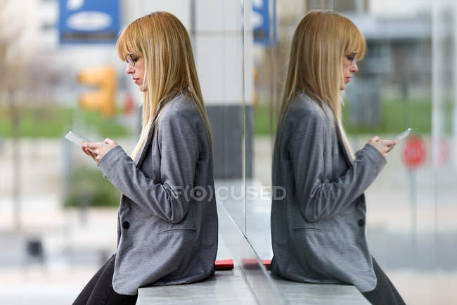 Young blond woman leaning on wall on street and using smartphone — Stock Photo