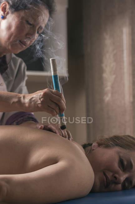 Terapista che esegue il trattamento di moxibustione in sala massaggi — Foto stock